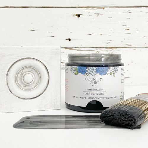 Jar of graphite black furniture glaze with brush stroke showing color and sample board