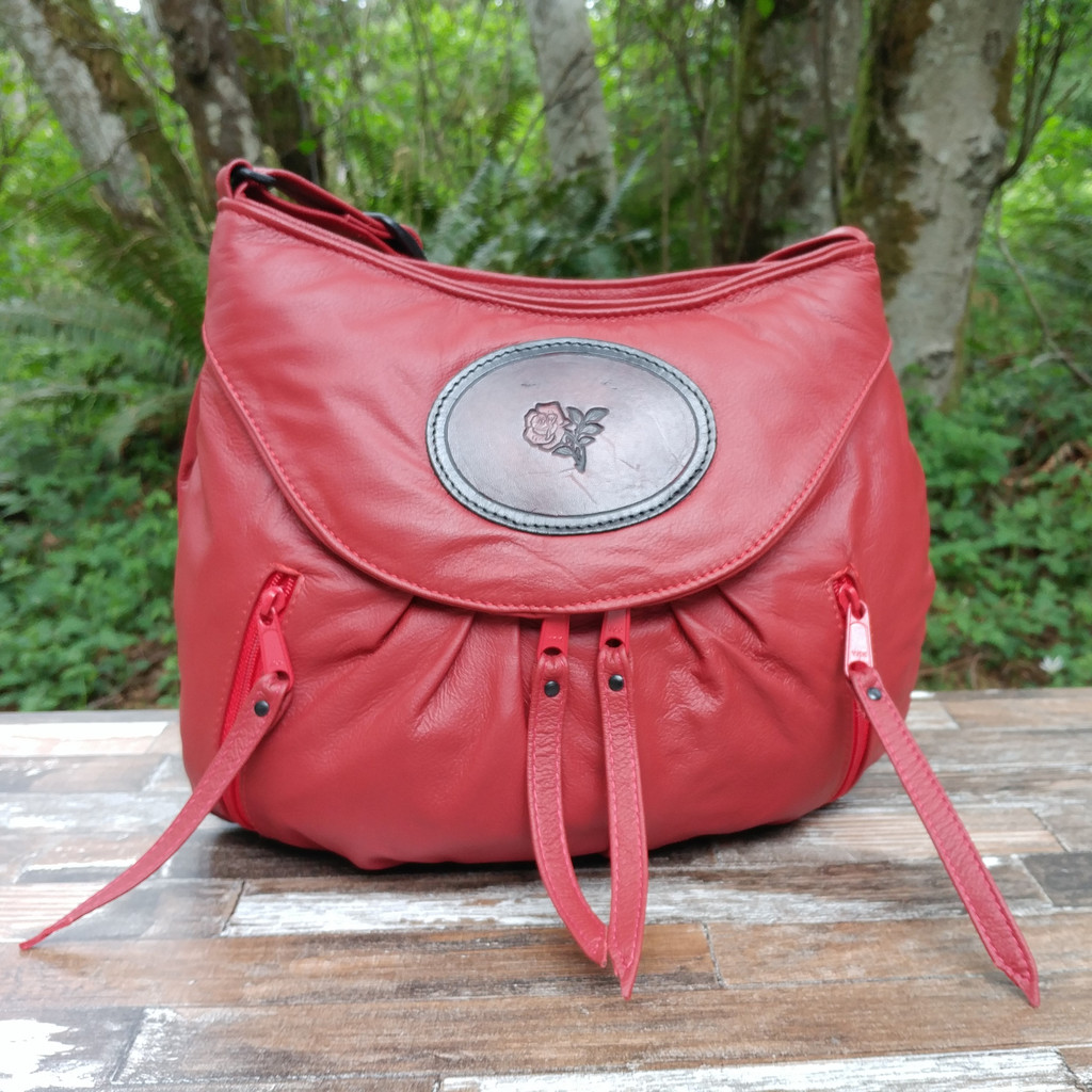 Red is striking beautiful color to wear.  It will go with everything Navy goes with including black. The accent of the tooled rose medallion on the front is the perfect touch.