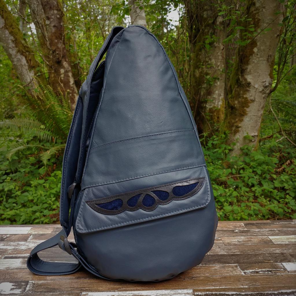 Large TravelMate,  Roomy enough for a small tablet,  hard back book, a jacket, most anything you would need for the day.  Fits better on a person with a longer back, usually someone taller.