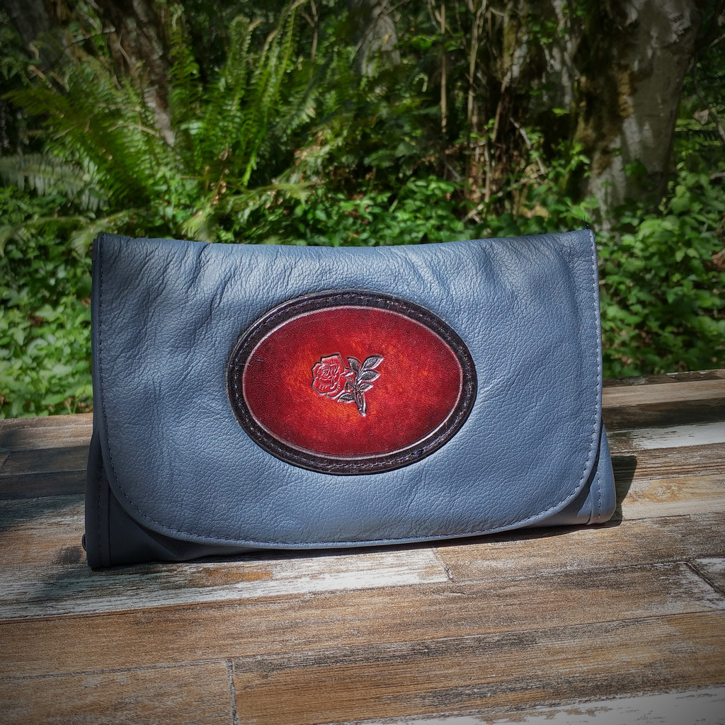 Navy Strapped Wallet with Tooled Rose Medallion.  Combines the elegant look and quality of soft leather with a Tooled chromed latigo front flap.
