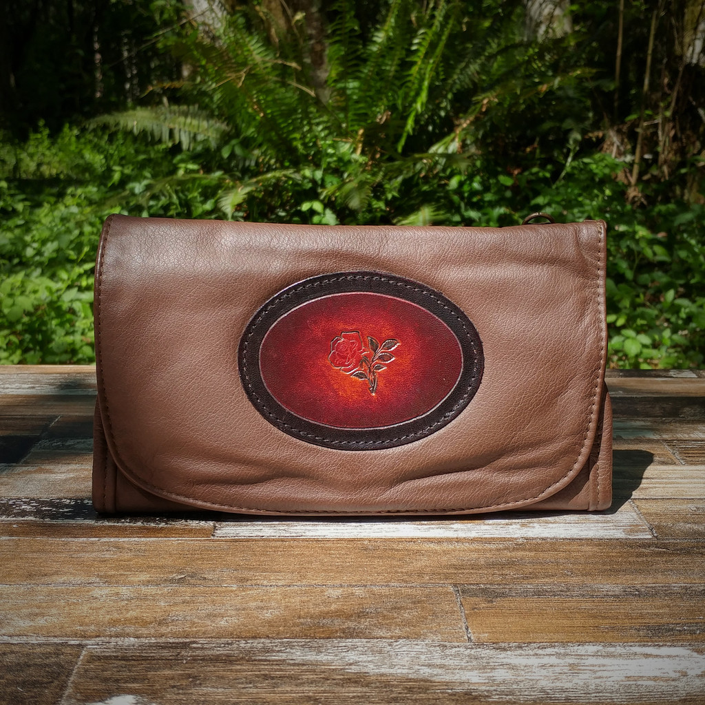 Brown Strapped Wallet with Tooled Rose Medallion.  Combines the elegant look and quality of soft leather with a Tooled chromed latigo front flap.