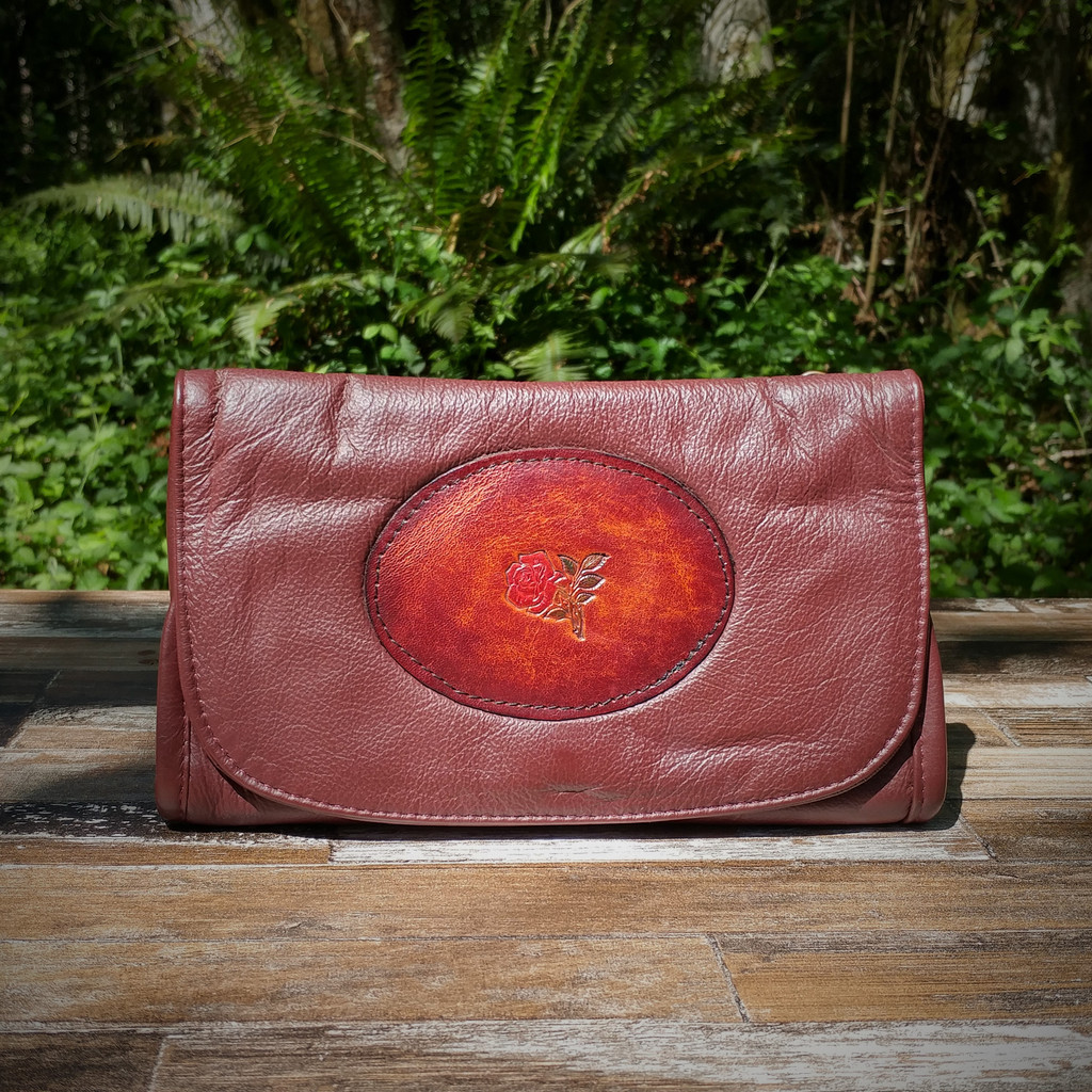 Burgundy Strapped Wallet with Tooled Rose Medallion.  Combines the elegant look and quality of soft leather with a Tooled Leather Medallion on the front flap.