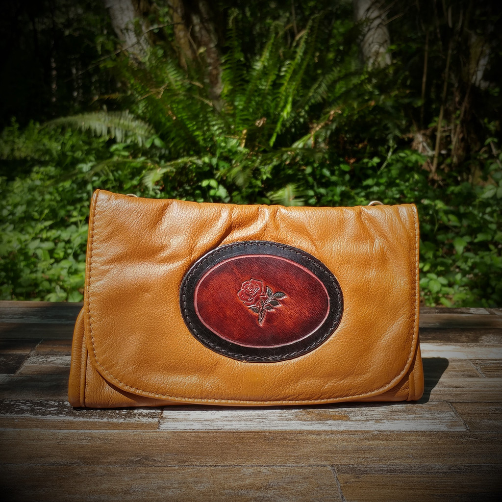 Cognac Strapped Wallet with Tooled Rose Medallion.  Combines the elegant look and quality of soft leather with a Tooled Leather Medallion on the front flap.