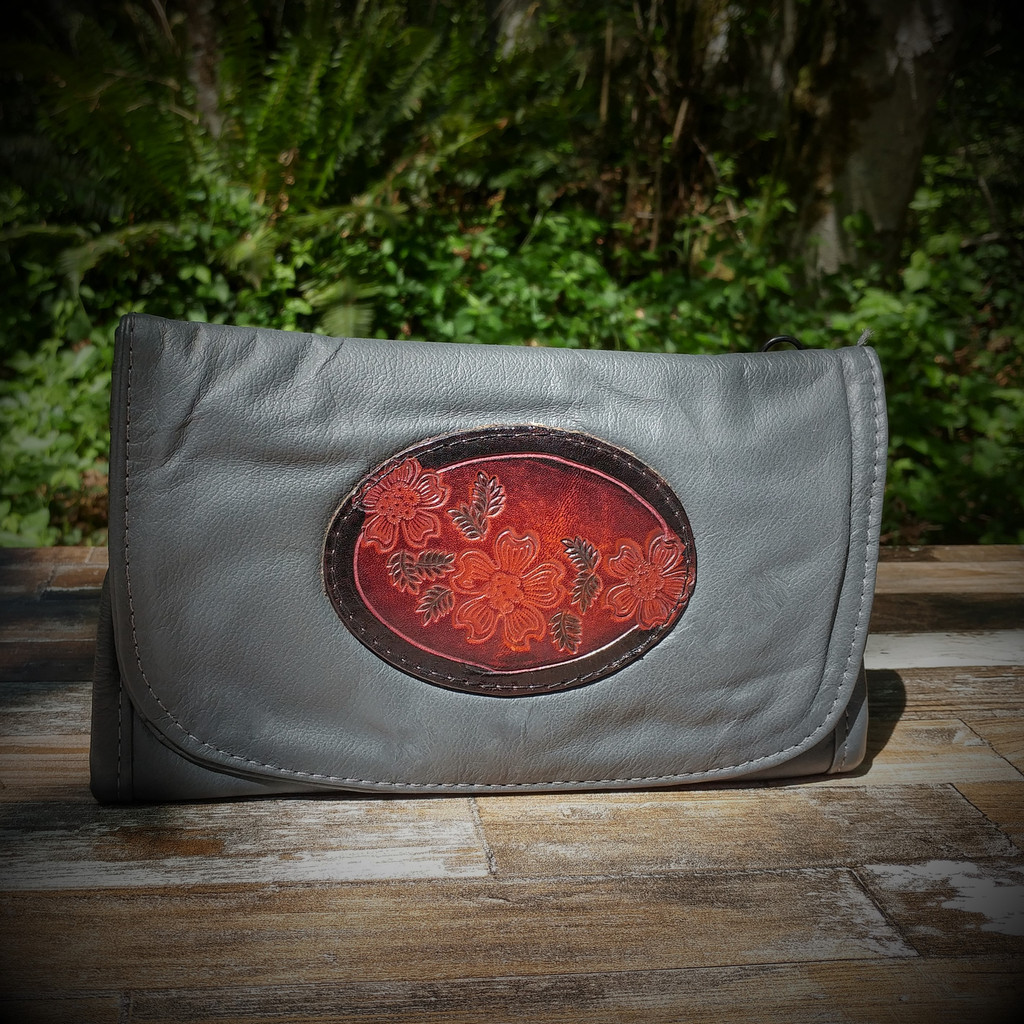 Grey Strapped Wallet with Tooled Dogwood Medallion.  Combines the elegant look and quality of soft leather with a Tooled Leather Medallion on the front flap.
