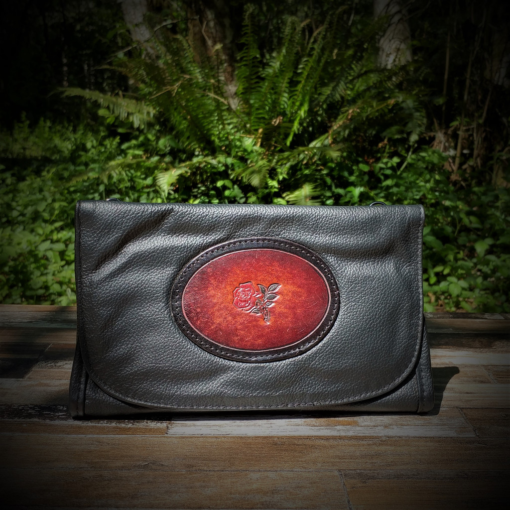 Black Strapped Wallet with Tooled Rose Medallion.  Combines the elegant look and quality of soft leather with a Tooled Leather Medallion on the front flap.
