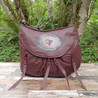 Burgundy is very neutral.  It will go with everything Navy goes with including black. The accent of the tooled rose medallion on the front is the perfect touch.