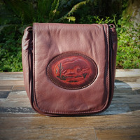 "Cognac Brown ""Little Black Purse"" with Tooled Running Horse.  Combines the elegant look and quality of soft leather with a Tooled chromed latigo front flap."