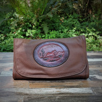 Dark Brown Strapped Wallet with Tooled Running Horse Medallion.  Combines the elegant look and quality of soft leather with a Tooled chromed latigo front flap.