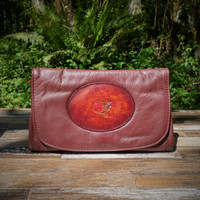 Burgundy Strapped Wallet with Tooled Rose Medallion.  Combines the elegant look and quality of soft leather with a Tooled chromed latigo front flap.