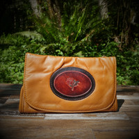 Cognac Strapped Wallet with Tooled Rose Medallion.  Combines the elegant look and quality of soft leather with a Tooled chromed latigo front flap.