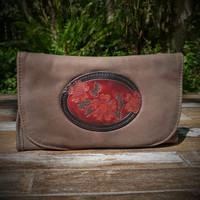 Distressed Brown Strapped Wallet with Tooled Dogwood Medallion.  Combines the elegant look and quality of soft leather with a Tooled Leather Medallion on the front flap.