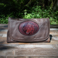 Distressed Brown Strapped Wallet with Tooled Double Horse Heads Medallion.  Combines the elegant look and quality of soft leather with a Tooled Leather Medallion on the front flap.