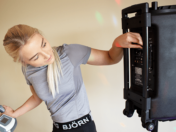 Aerobics fitness instructer showing you how to easily use a portable pa audio speaker system during a class
