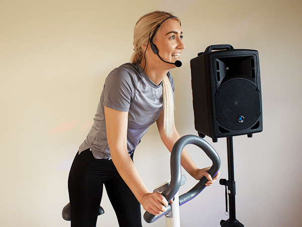 Portable pa system speaker on speaker stand with wireless headset microphone on gym instructor during a spin fitness class