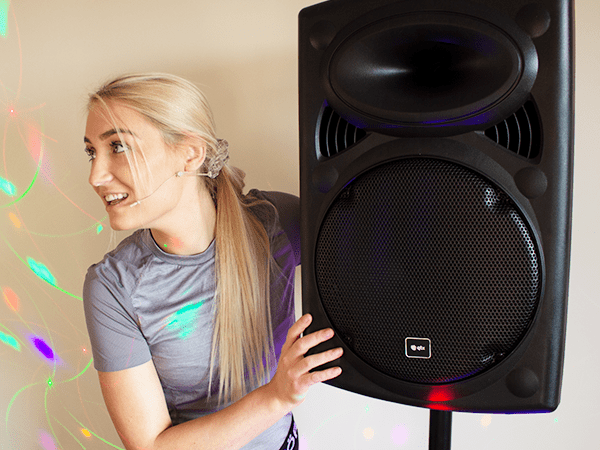 zumba fitness instructor with portable pa speaker system for zumba class with skin coloured headset microphone on