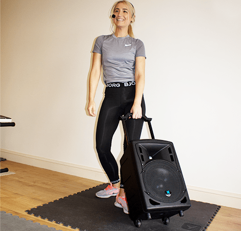 The Best Sound System for Aerobics with Aerobics instructer pulling a speaker with wheels