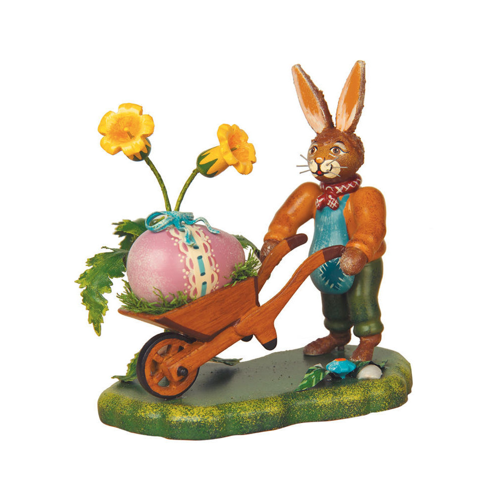 Bunny figure with Easter Egg and daffodils in wheel barrow