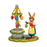 Mrs. Rabbit is decorating the village fountain with colorful ribbons and eggs for Easter.