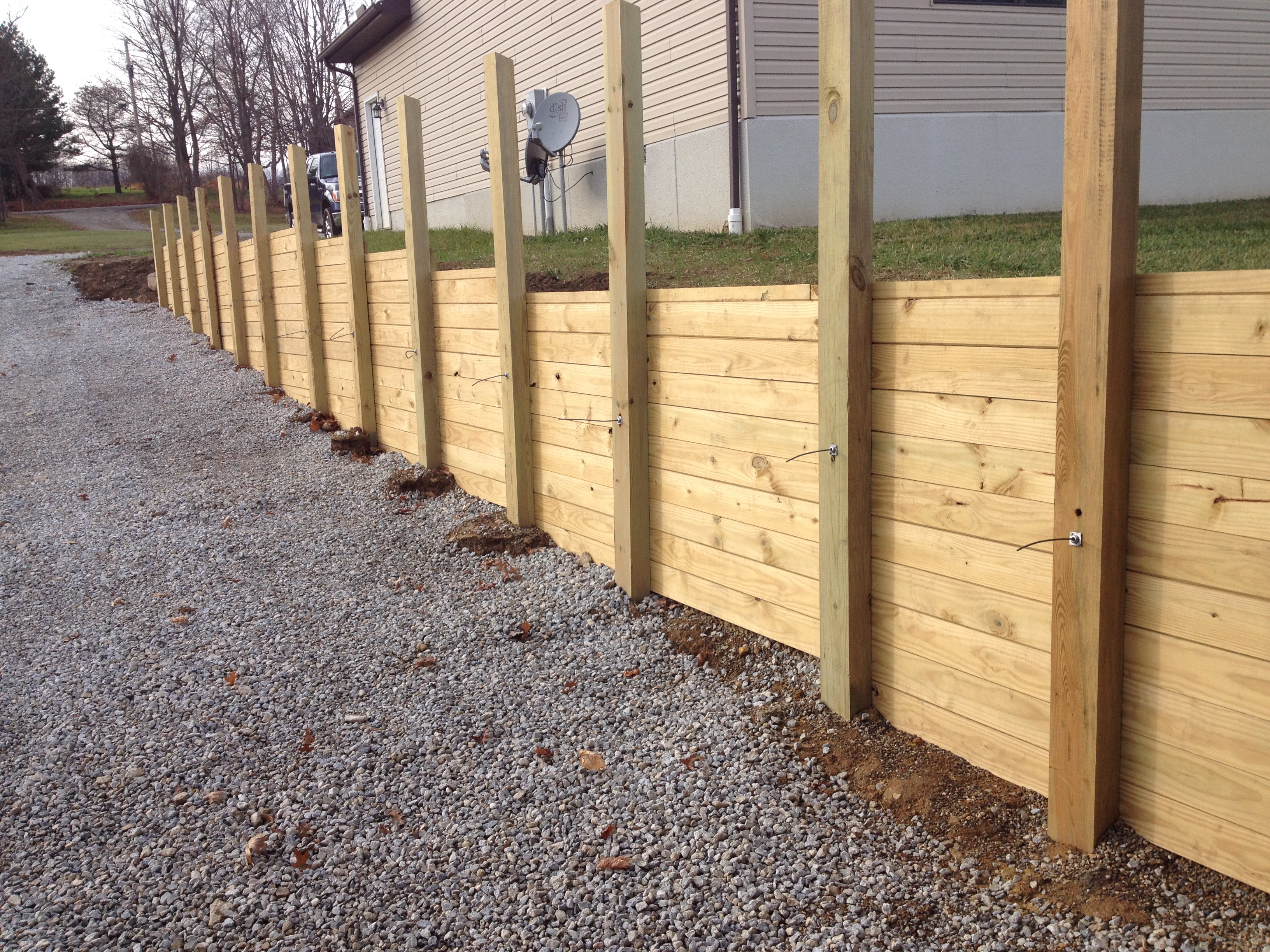 Retaining wall secured by aluminum bullet anchors