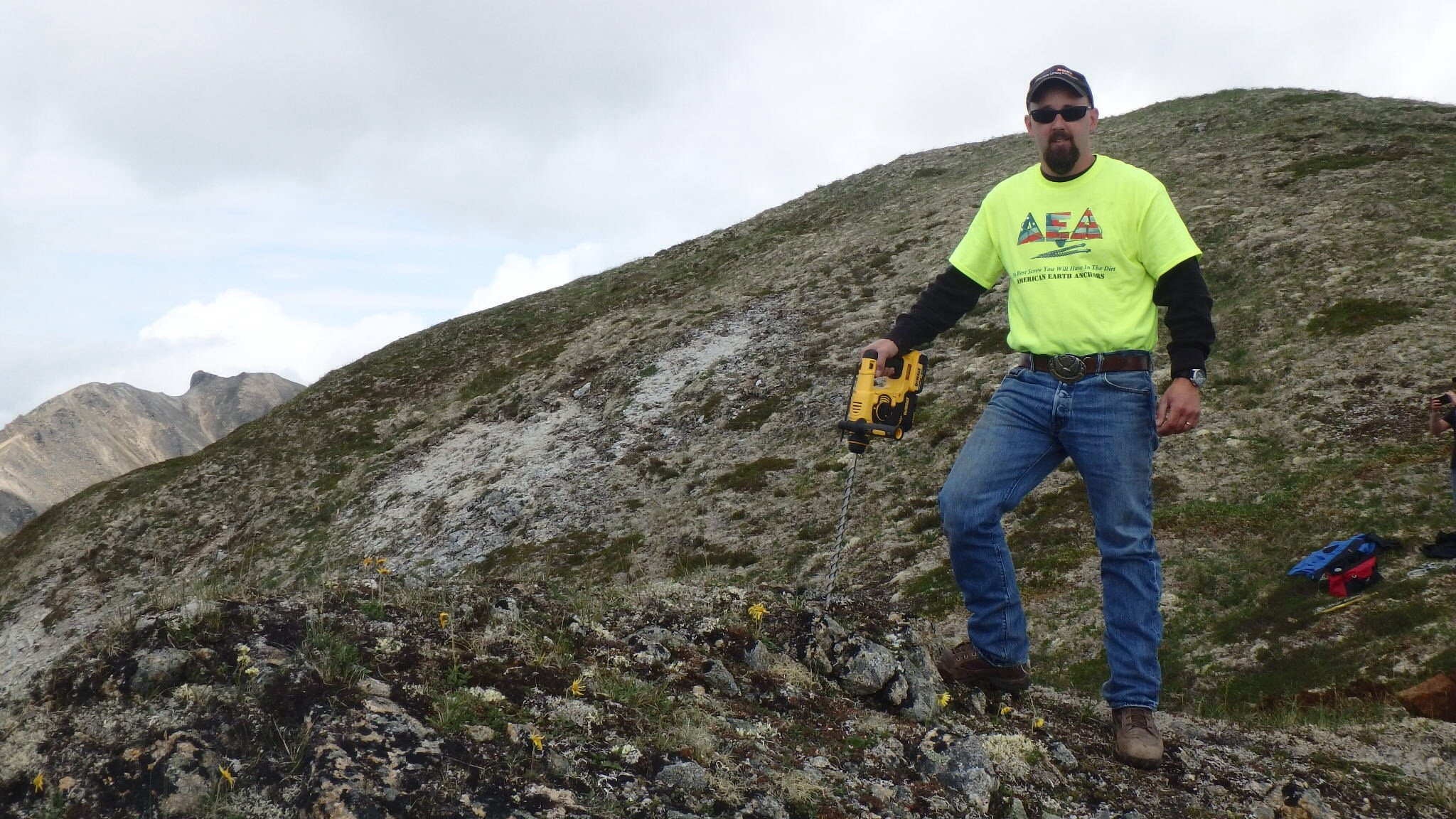 Pre-drilling into rock soil on mountain side before insalling bullet anchors