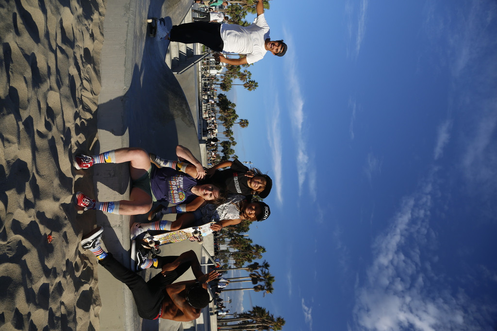 friends hanging out with skys the limit custom for a cause pride socks in venice beach, california.