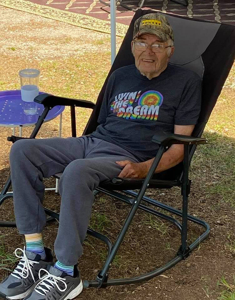 our oldest customer is 90 rocking his pride socks living the dream shirt while camping outside.