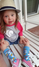 Baby girl rocking out her pride socks designed by rubys rainbow to help students with down syndrome attend college.