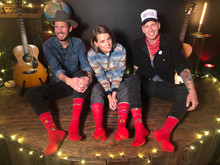brandi carlile and the twins take a photo in their pride socks to benefit looking out foundation