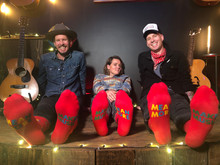 brandi carlile and the twins take a photo in their studio in seattle in the band together socks from pride socks to benefit looking out foundation