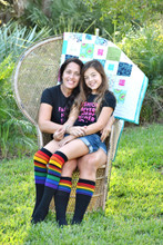 mom and daughter wearing matching pride socks.