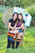 mom and daughter wearing matching pride socks.