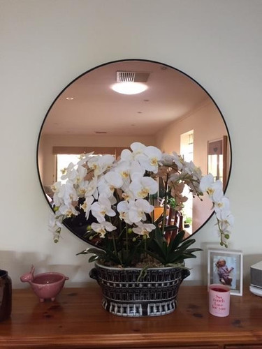 Modern Round Circular Mirror with copper tint, in a room