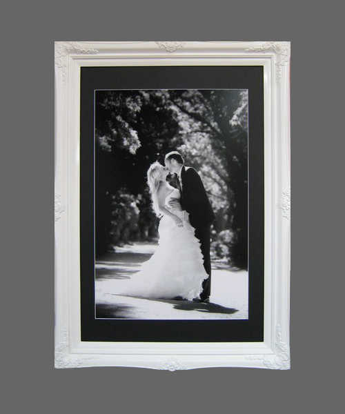 Wedding photo framed in a modern looking high gloss white ornate frame
