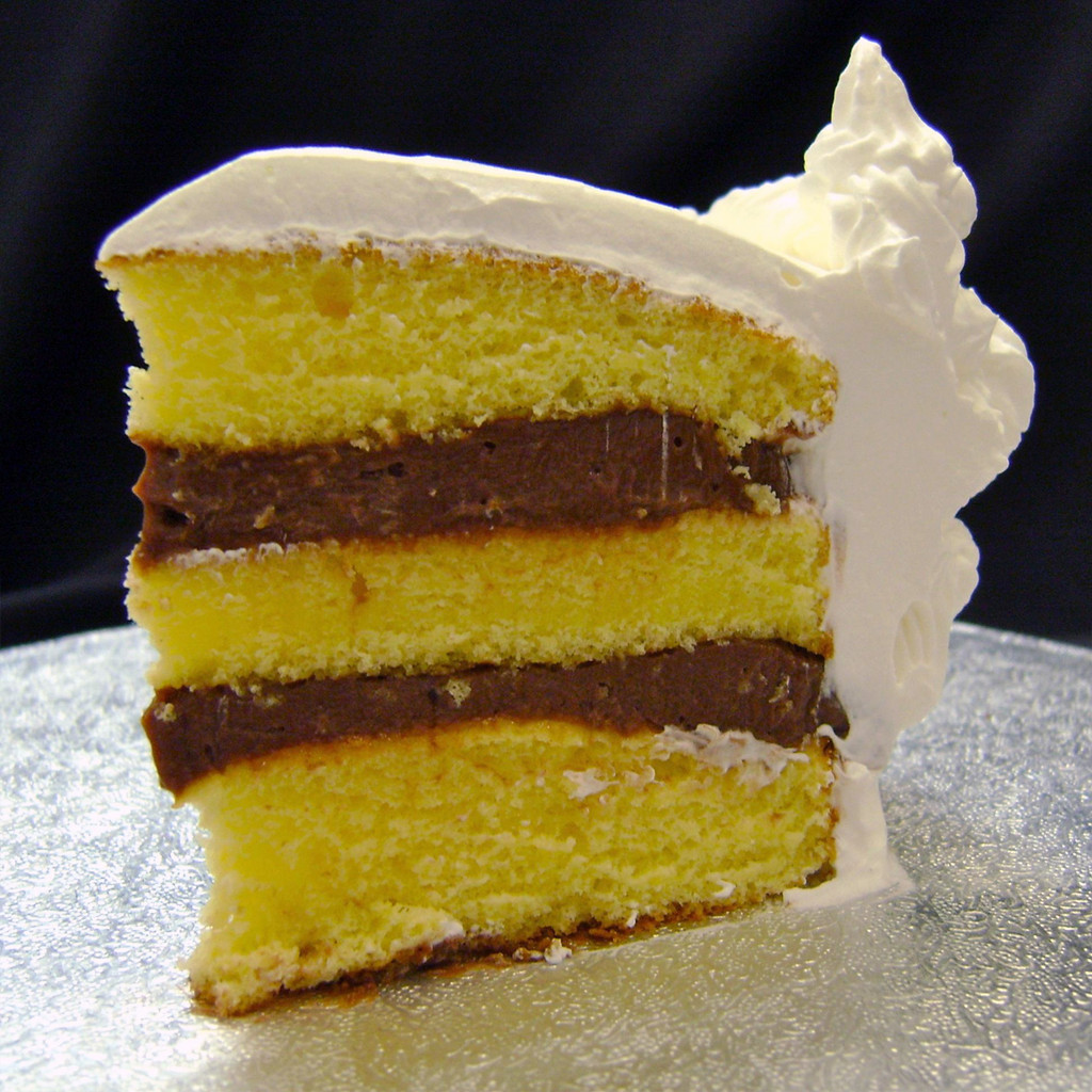 Chocolate Rum: three moist layers of Yellow cake filled with signature Italian (non-alcoholic) Chocolate Rum custard, frosted in Italian whipped cream.