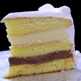 Rum Marble: three moist layers of Yellow cake filled with one layer of signature Italian (non-alcoholic) Rum custard and one layer of Chocolate Rum custard, frosted in Italian whipped cream.