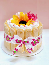Cathy's classic holiday design for Mother's Day. Featuring lady fingers around the cake wrapped like a package with a bow and non-edible silk flowers on top.