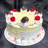 Drip cake with crushed Oreo cookies, colorful sprinkles, and cherries on top.