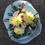 Pastel yellows and pinks in a hand tied bouquet.