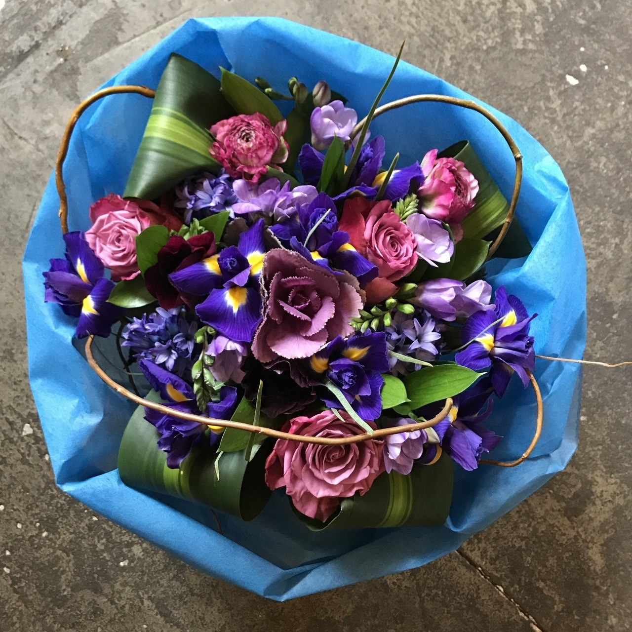 Seasonal purples and blues in a hand tied roll wrapped bouquet.