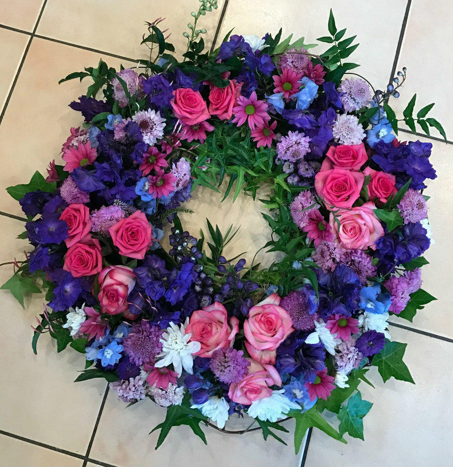 Sympathy wreath made with roses and seasonal blue flowers, with ferns and Ivy.