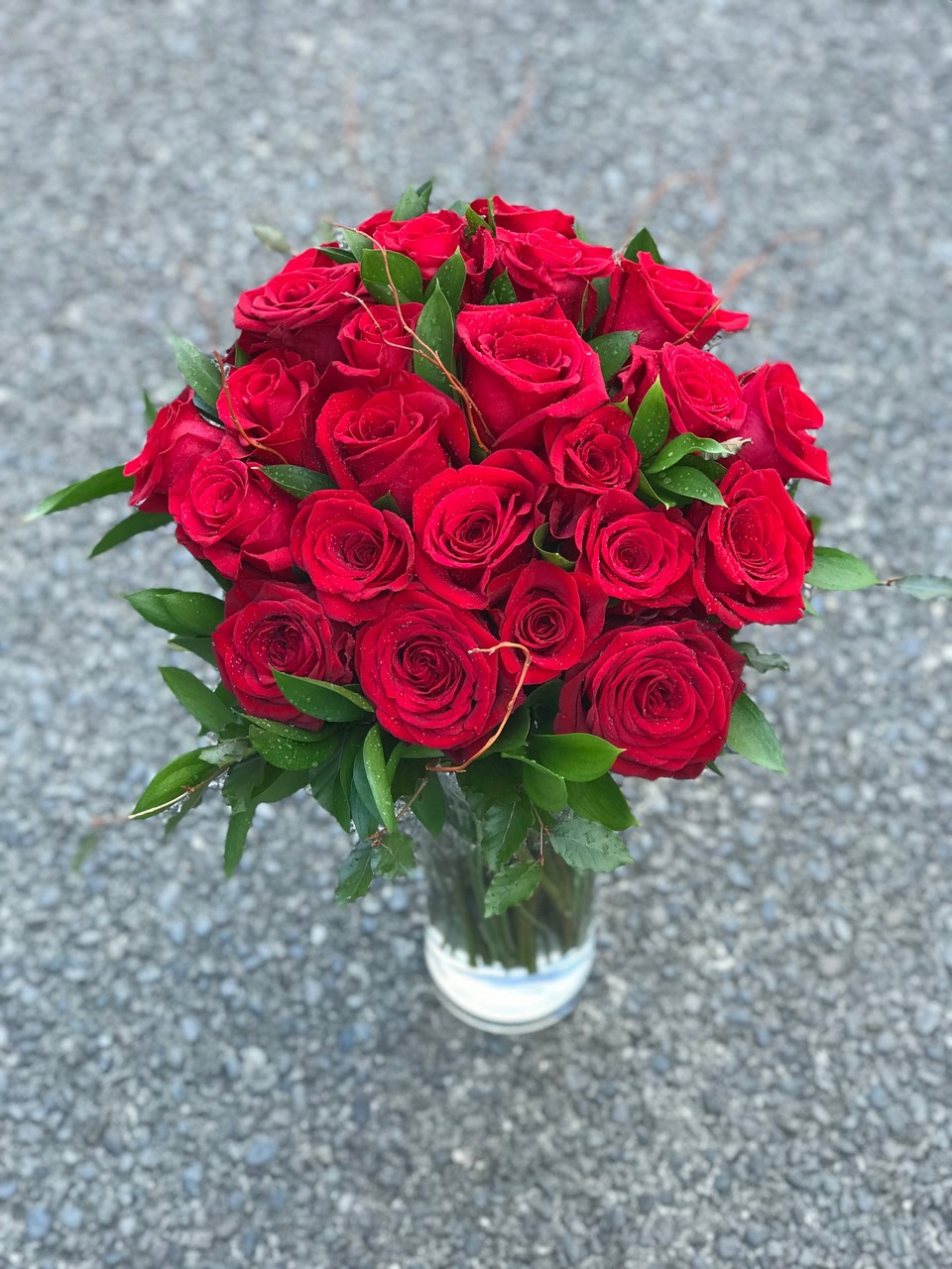 Two dozen red roses presented with seasonal foliage in a complimentary vase.