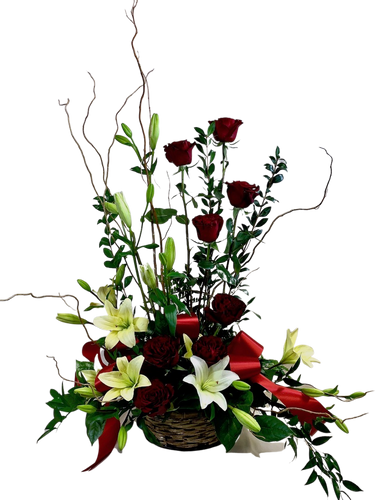 Majestic Tribute:  sympathy arrangement of deep red roses, white lilies, curly willow, and seasonal greens, in a dark willow basket