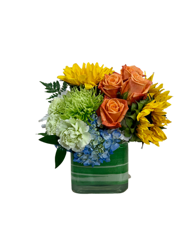 Rockin' the Union:  arrangement of sunflowers, orange roses, and blue hydrangea in a leaf-wrapped glass cube