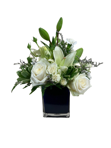 Among the Clouds:  all-white arrangement of roses, lilies, spray roses, and miniature carnations in a cube of sapphire blue glass.