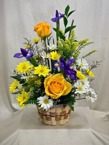 Celebrations Basket:  arrangement of purple iris, yellow roses, and yellow and white daisies in a round woven basket