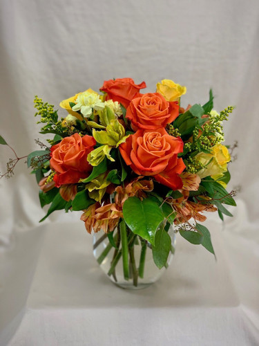 Sunset Over Strawbridge Lake:  Arrangement of orange and yellow roses, alstromeria, and solidago, in a clear glass vase
