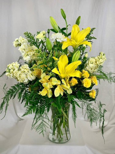 Lemon Sorbet:  Arrangement of yellow lilies, yellow spray roses, cream stock, and cream carnations, in a clear glass gathering vase