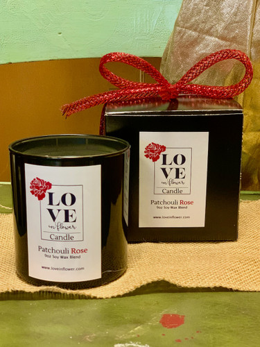 Rose-scented candle by Love in Flower.  Nine-ounce artisan candle, made from a blend of soy and coconut waxes,  and presented in black gift box with red ribbon trim.