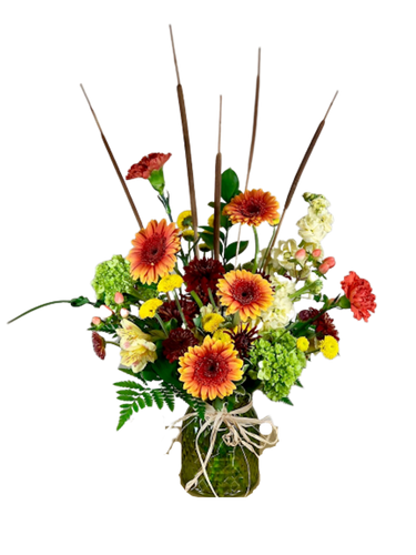 Pencil Me In:  arrangement of pencil cattails, orange gerbera, green hydrangeas, cream stock, and more, in a vase of olive-green faceted glass