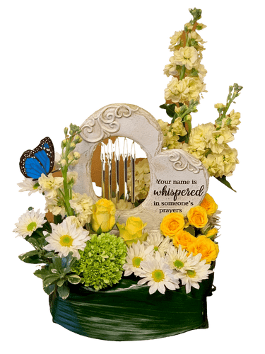 Garden of Memories:  Heart-shaped windchime keepsake surrounded by fresh flowers in tones of white, yellow, and green.